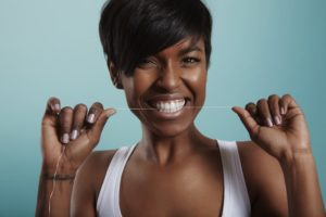 Smiling woman flossing her beautiful, healthy teeth